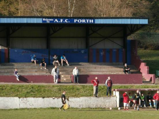 Everyone watches on, including club secretary Huw from his perch on the wall next to the dugout.