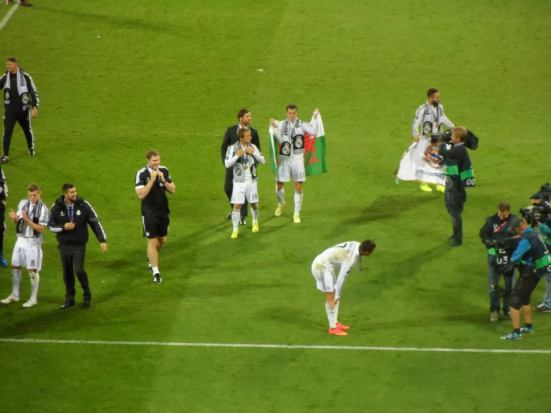 Lap of honour - Bale in his Welsh flag.